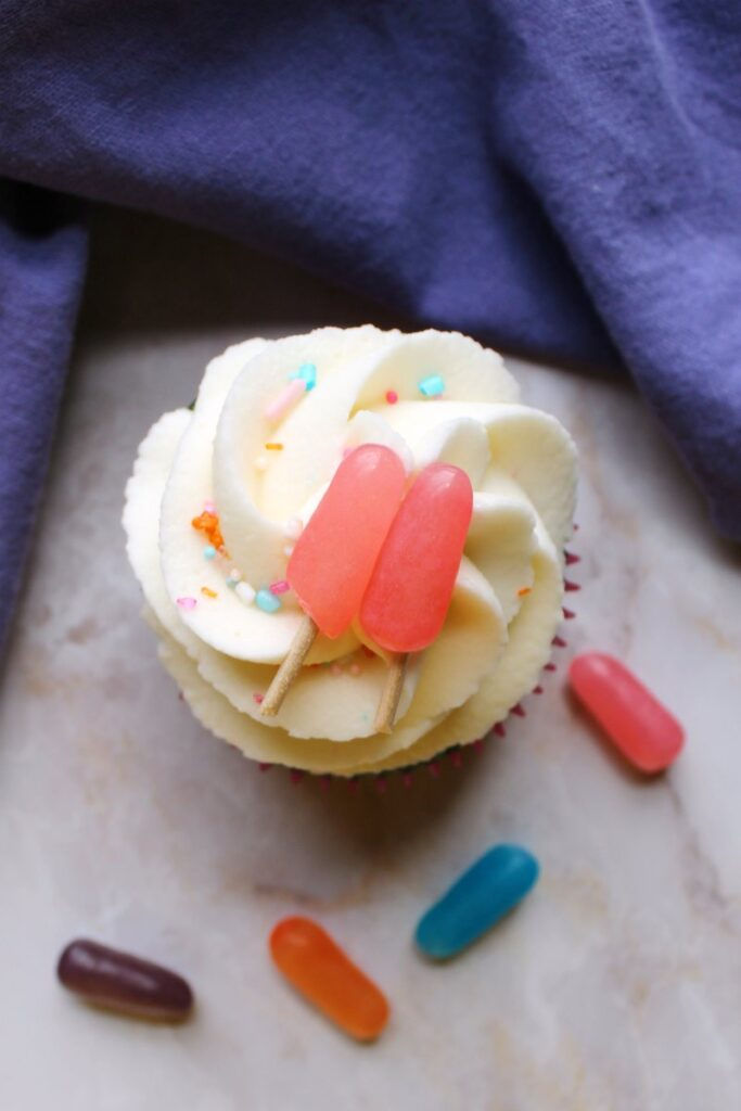 looking down at summery cupcake with fluffy white frosting and pink candy popsicle topper.