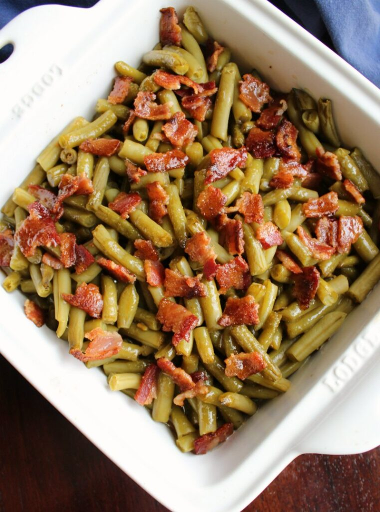 square pan of green beans and bacon smothered in delicious sauce straight from the oven.