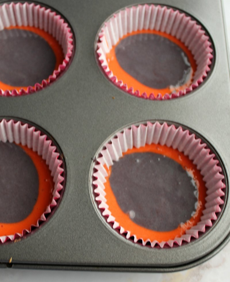 pink and purple cupcake batter in cupcake liners in tin.