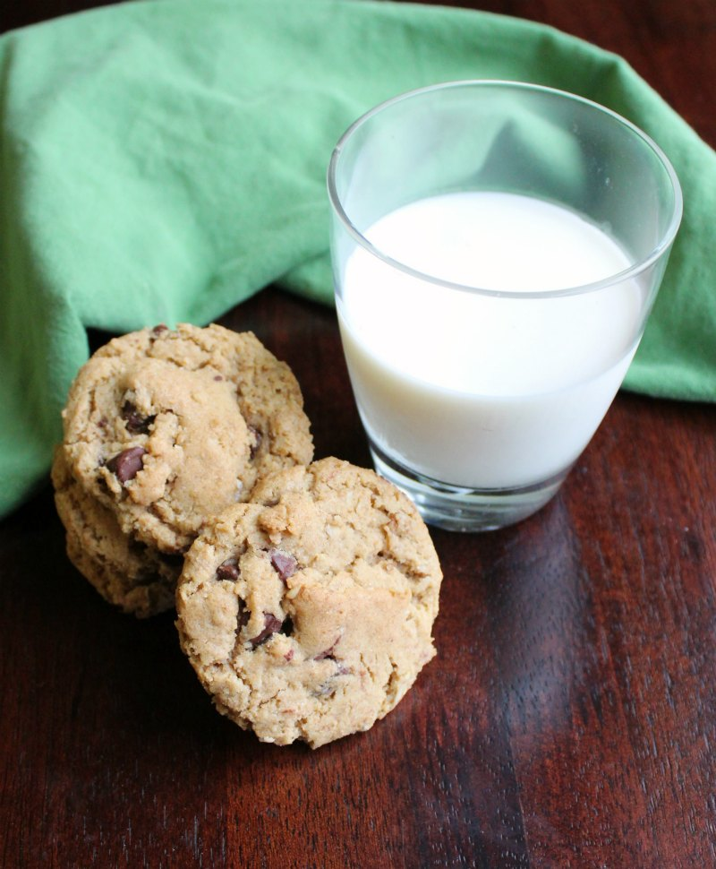 stack of brown butter cowgirl cookies next to a glass of milk.