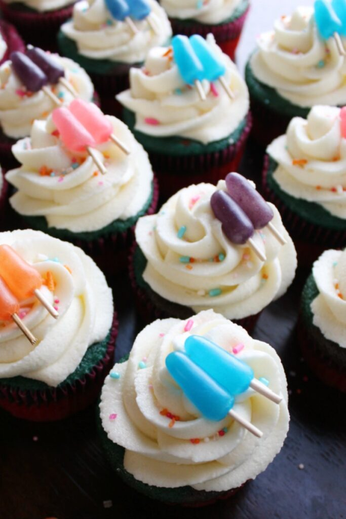 a bunch of sweet summertime cupcakes with swirls of cream cheese frosting and mike and ike popsicle toppers .