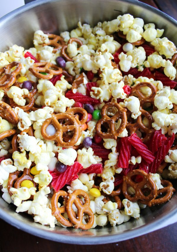 Big mixing bowl full of popcorn, pretzels and candy for snack mix.