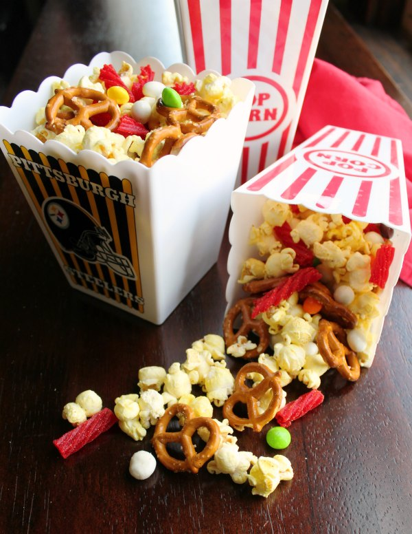 small popcorn tubs full of movie theater snack mix with popcorn and candy