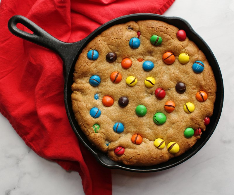 close up of peanut butter skillet cookie with peanut butter M&Ms baked on top