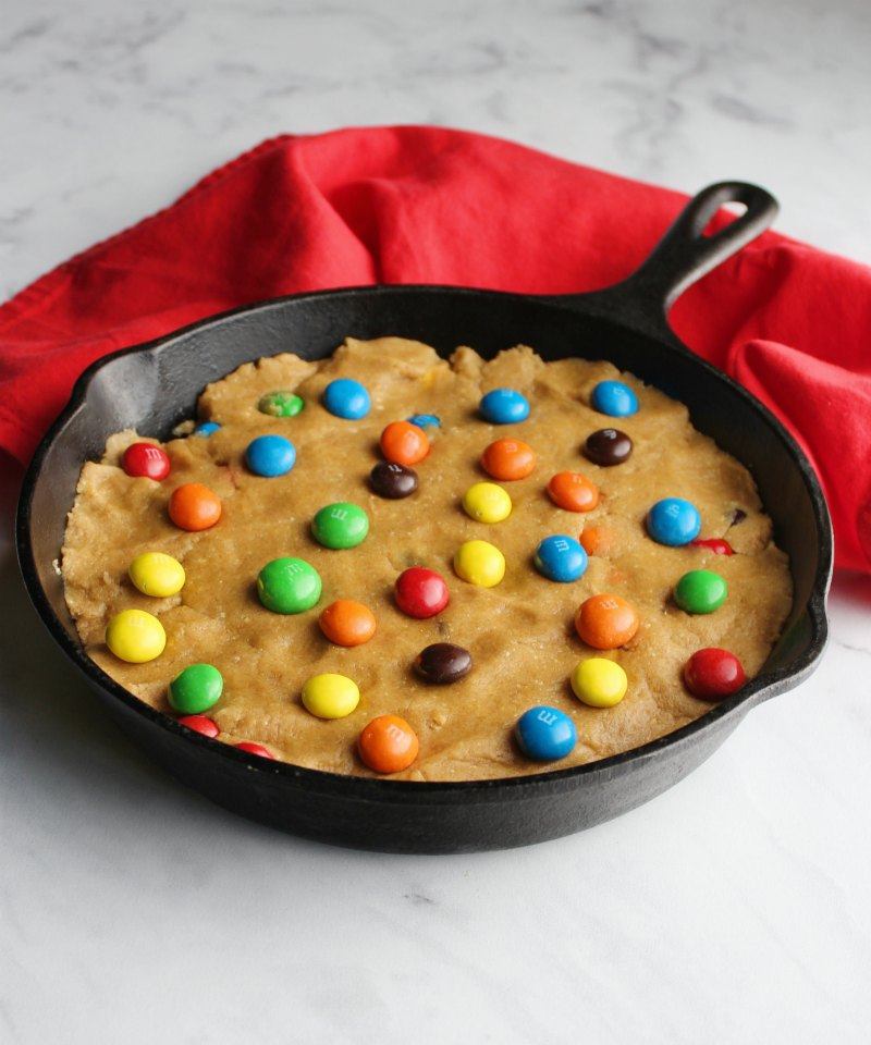cookie dough pressed into cast iron skillet with extra candies on top
