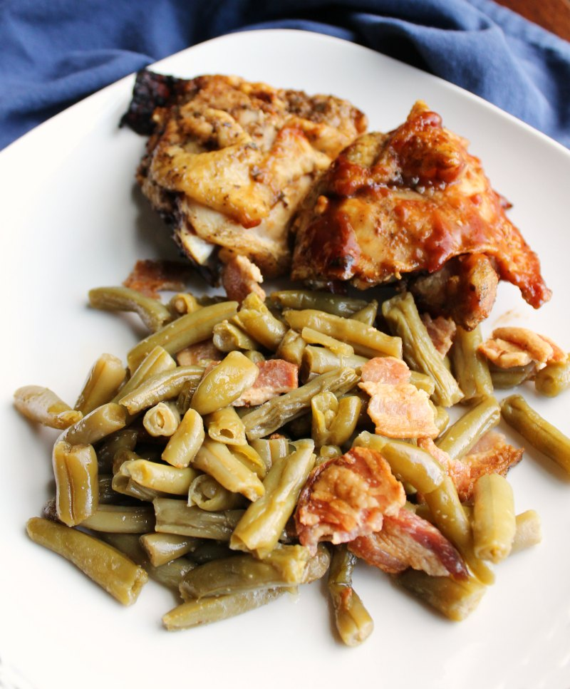 Dinner plate loaded with smothered green beans and bacon and bbq chicken.