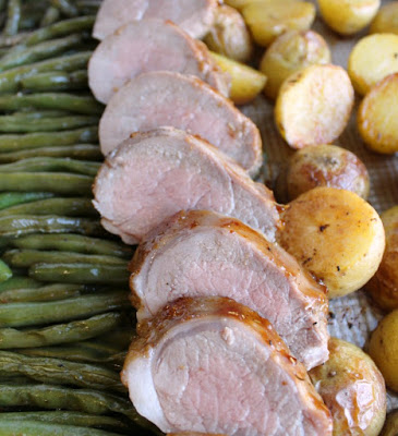 sheet pan filled with pink pork tenderloin slices, potatoes and green beans.