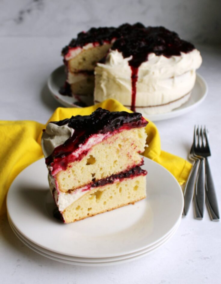 slice of blackberry shortcake cake served on plate with remaining cake in background.