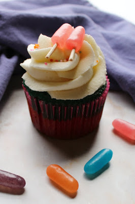 close up of cupcake with big swirl of cream cheese frosting and pink candy popsicle topper