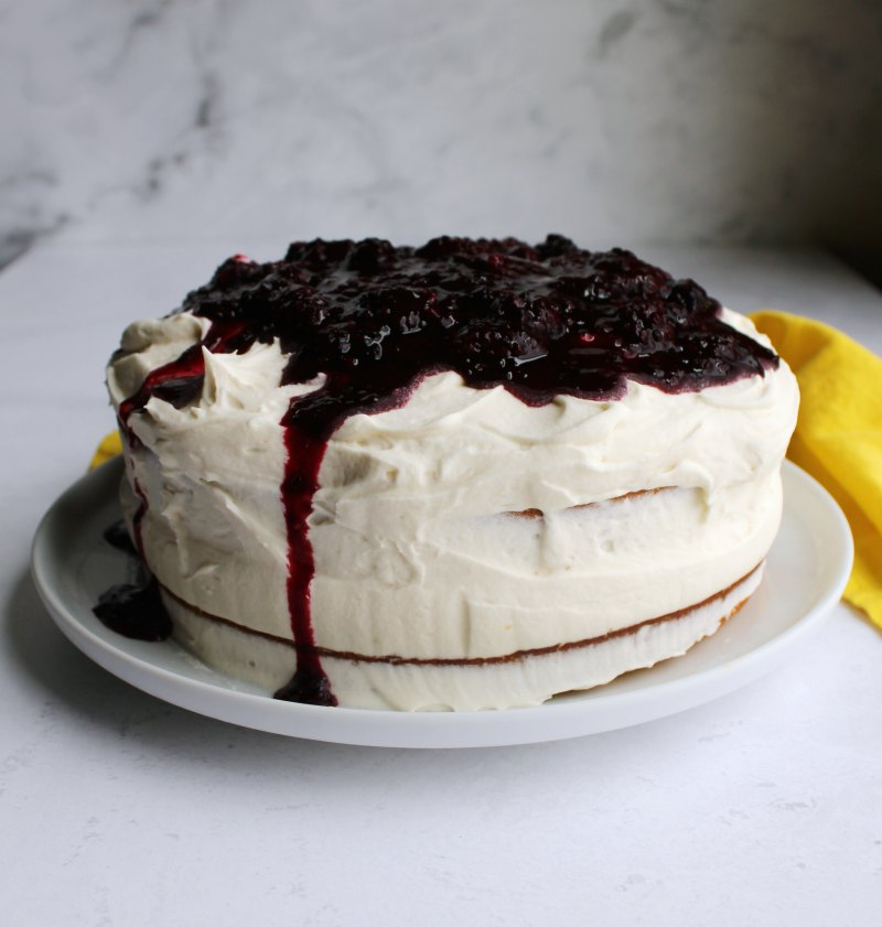 whole blackberry cake with lots of fluffy white frosting on top, barely frosted sides and some blackberry sauce dripping over the edge.