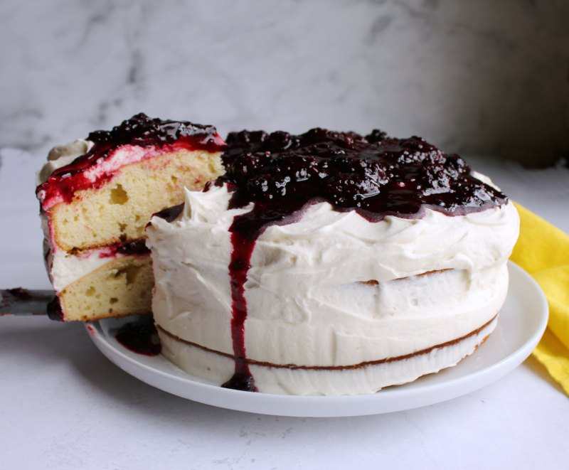 whole blackberry shortcake cake with first slice being removed.