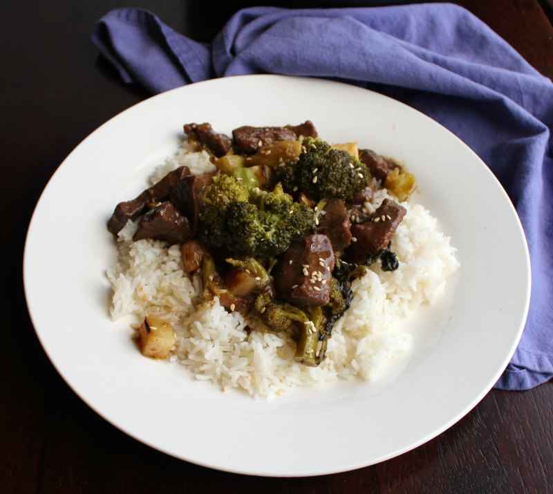 Plate of Chinese takeout style backstrap and broccoli served over rice.