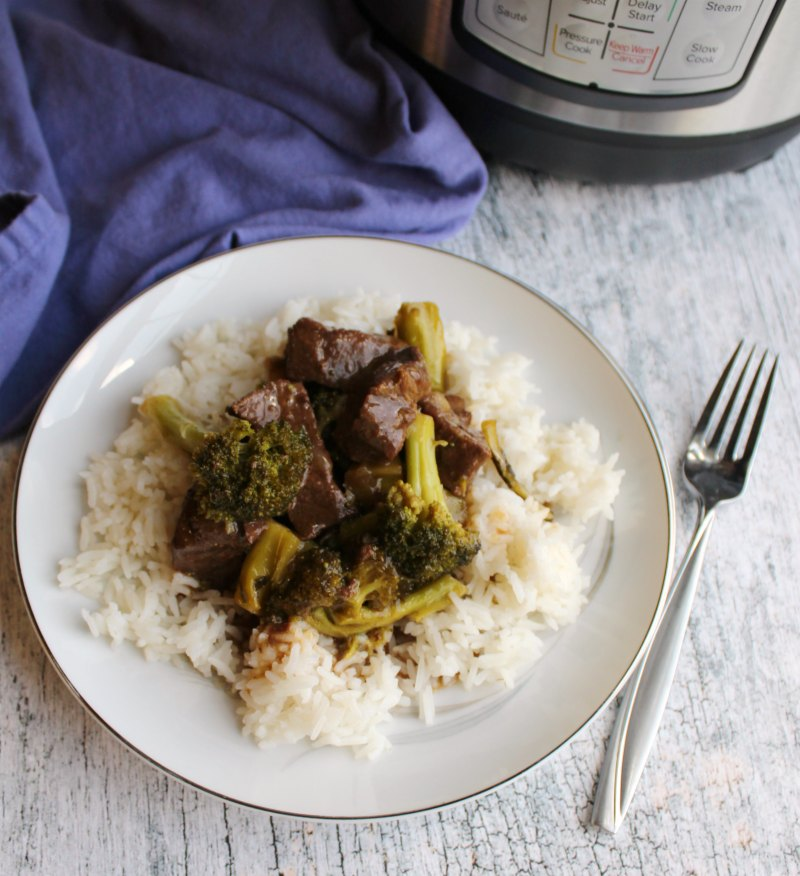 Plate of rice topped with cubes of backstrap and broccoli in brown sauce next to instant pot.