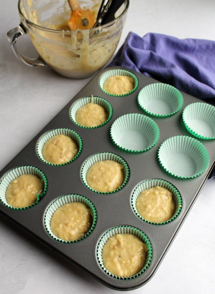 banana cupcake batter being scooped into cupcake liners to be baked.