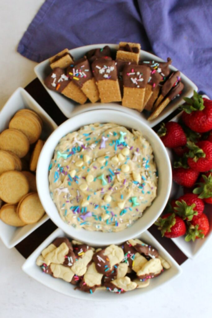 bowl of sprinkle filled birthday cookie dough dip with strawberries, golden oreos, graham crackers and animal crackers for dippers.