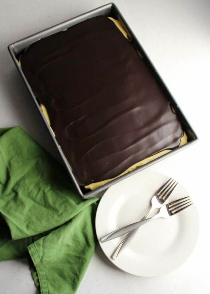Whole sheet cake topped with shiny chocolate ganache, ready to be served.