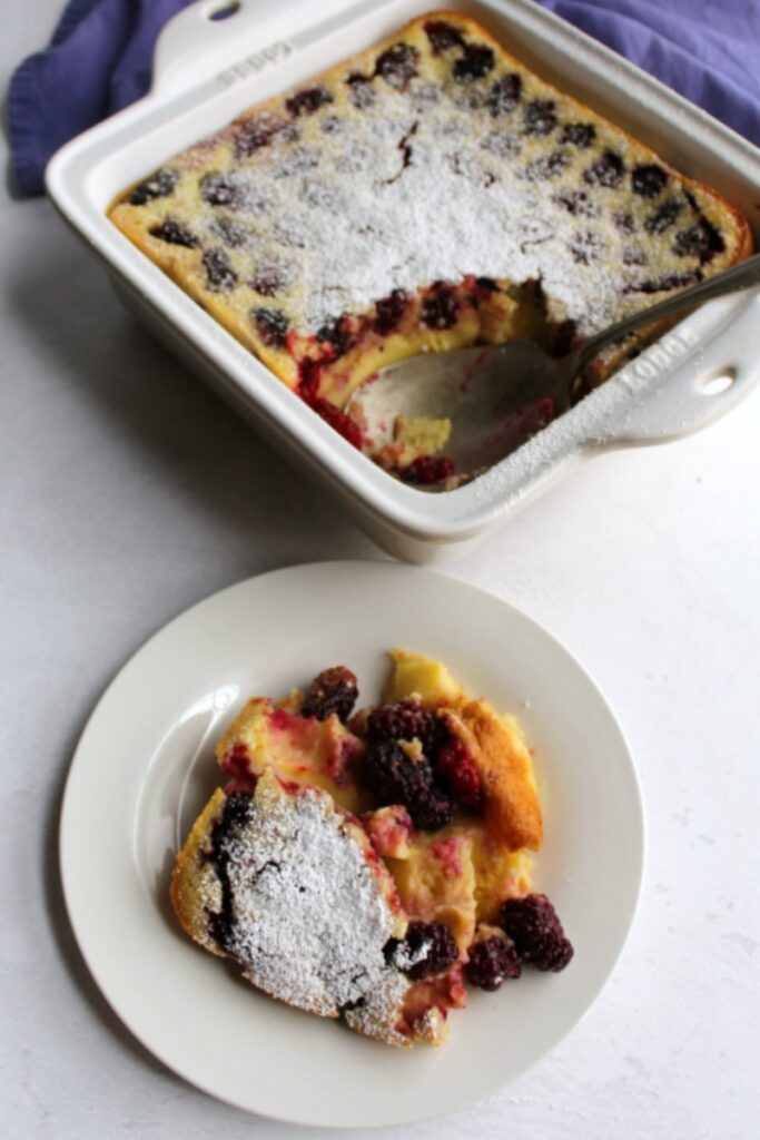 serving of blackberry clafoutis on plate in front of pan of remaining clafoutis.