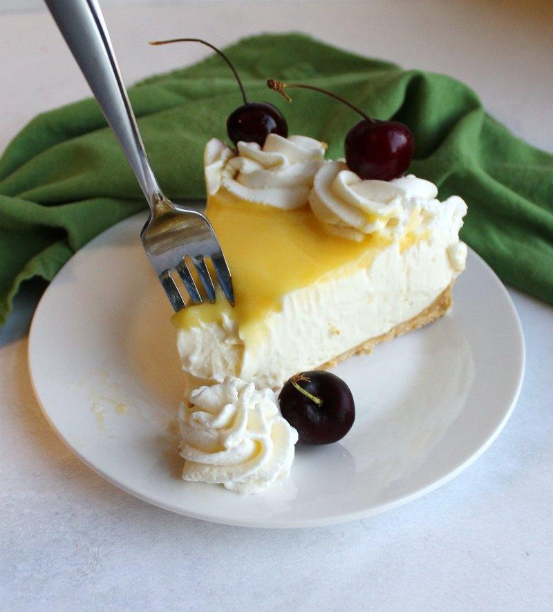 Fork going in for first bite of lemon no bake cheesecake slice.