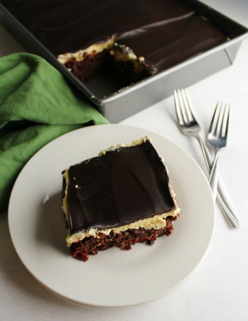 first piece of black forest cake on plate showing creamy vanilla frosting between chocolate cake and ganache topping.