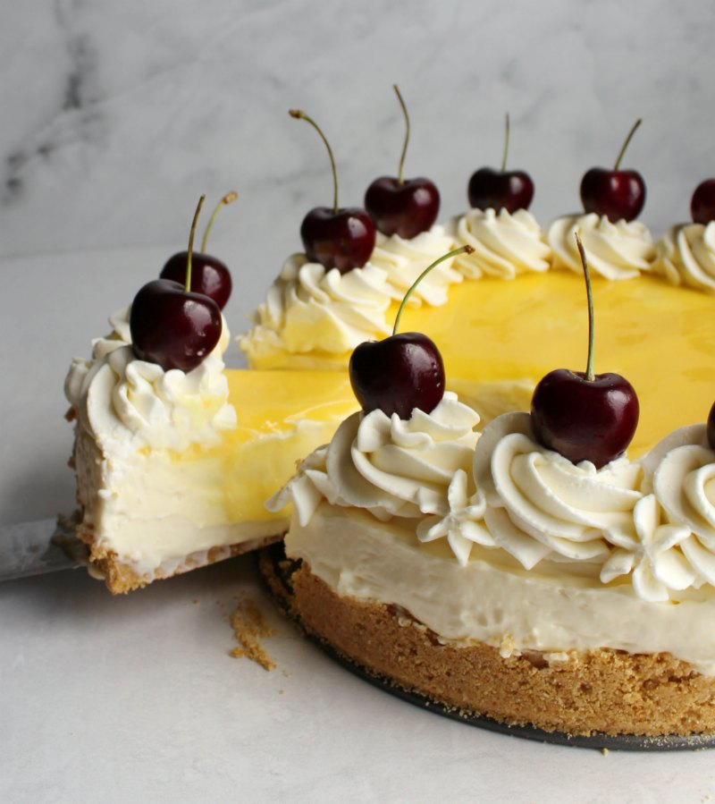 first slice being removed from lemon no bake cheesecake with swirls of cream cheese whipped cream and cherries