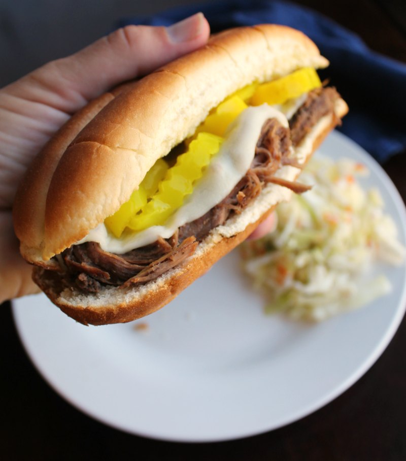 hand holding Italian beef roll with melted provolone and pepperoncini slices with plate and coleslaw in the background