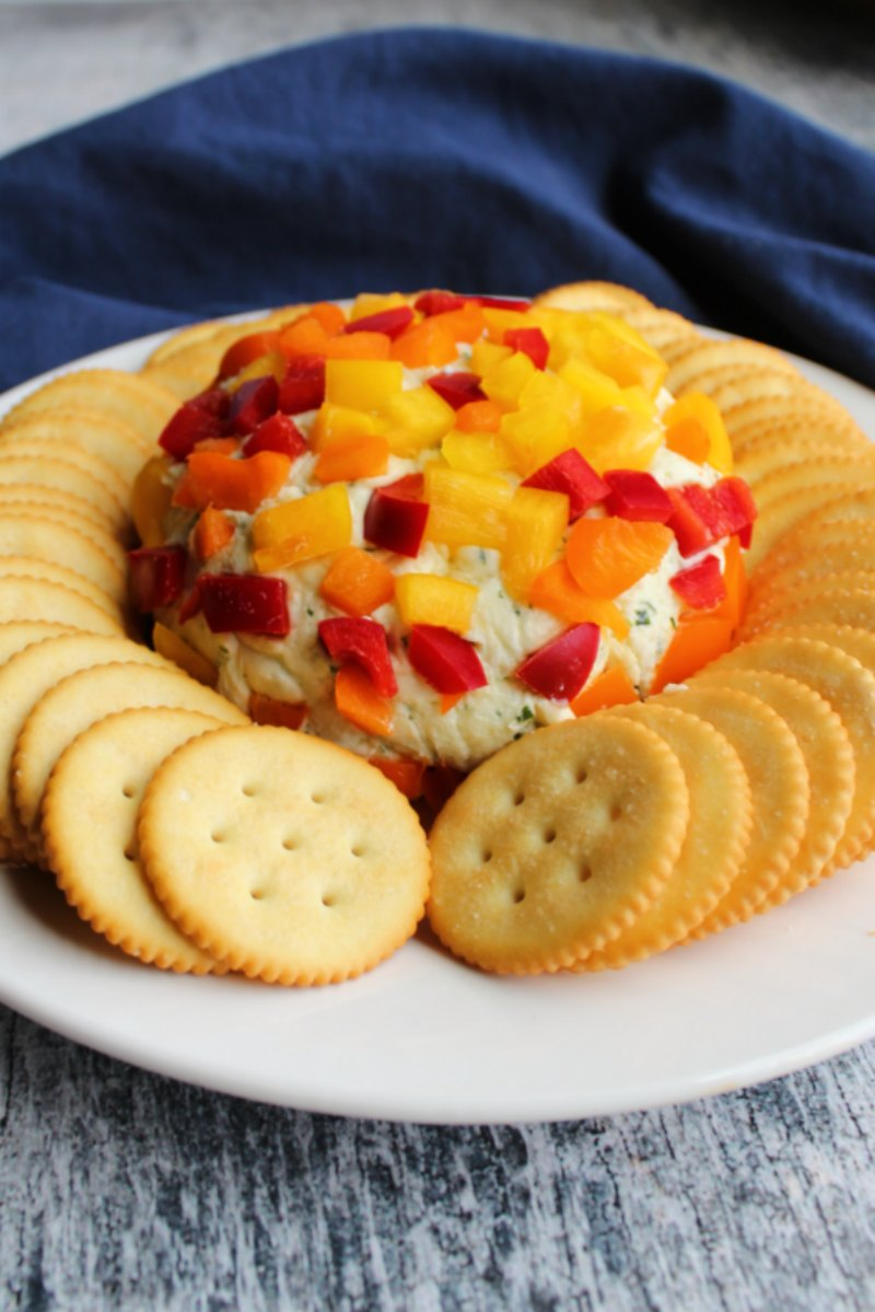 Havarti cheese ball with pieces of colorful sweet peppers on the outside with crackers, ready to eat.