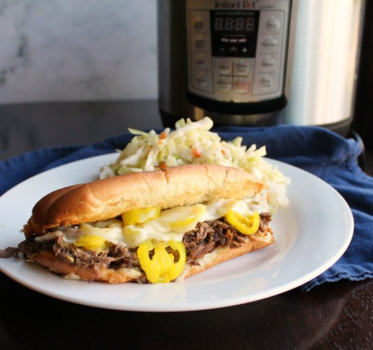 Plate of Italian beef sandwich an fresh coleslaw in front of instant pot.
