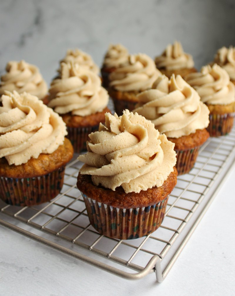 cooling rack full of banana cupcakes with swirls of peanut butter buttercream.