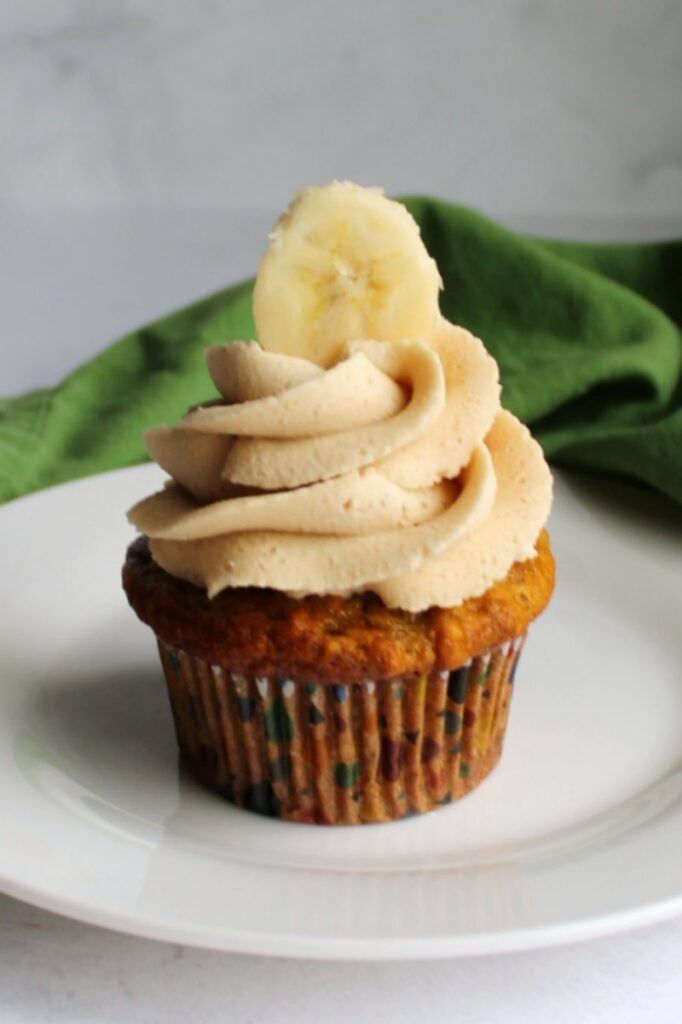 banana cupcake with swirl of fluffy peanut butter and brown sugar buttercream and a slice of banana on top.