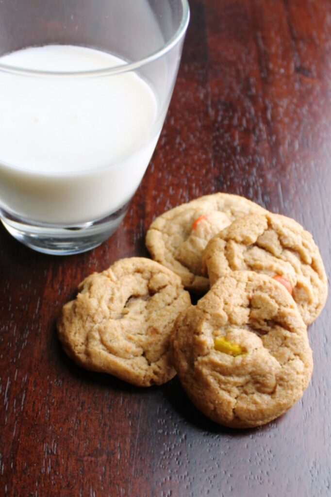 four triple peanut butter cookies next to a glass of milk.