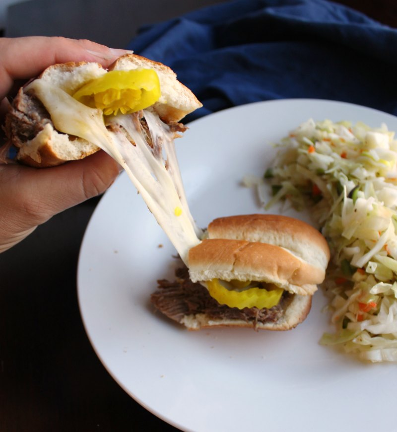 Italian beef sandwich ripped in half with provolone cheese pull.