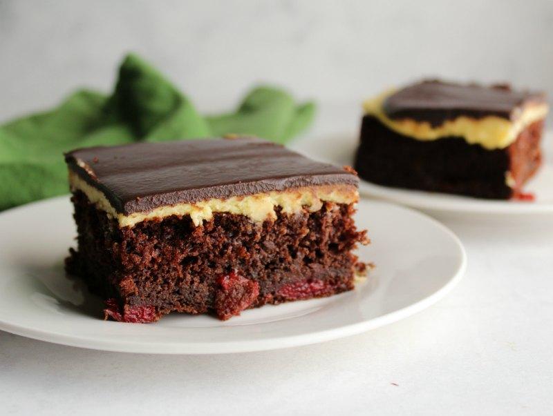 two dessert plates with a slice of black forest sheet cake on each, chocolate cake, german buttercream, dark chocolate ganache.