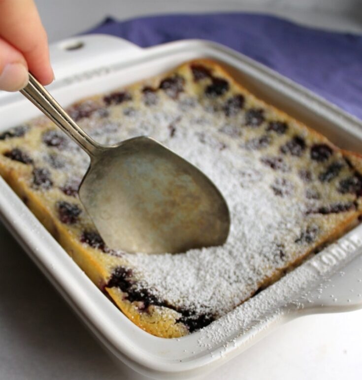 berry spoon going into pan of blackberry clafoutis covered with powdered sugar.