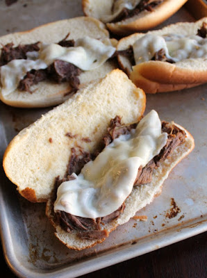 baking tray with toasted rolls pile with shredded Italian beef and melted provolone