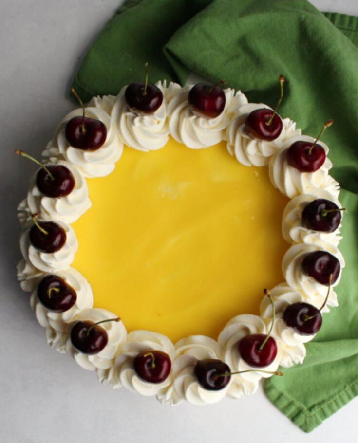 lemon no bake cheesecake topped with whipped cream swirls and fresh cherries.