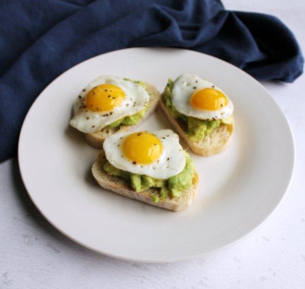 three avocado and quail egg crostini served on small plate.