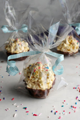 cellophane wrapped chocolate dipped marshmallow popcorn balls with sprinkles and curling ribbon