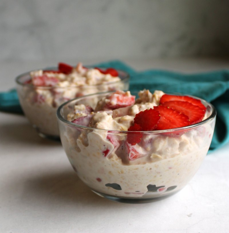 looking across two glass bowls of creamy strawberry overnight oatmeal.