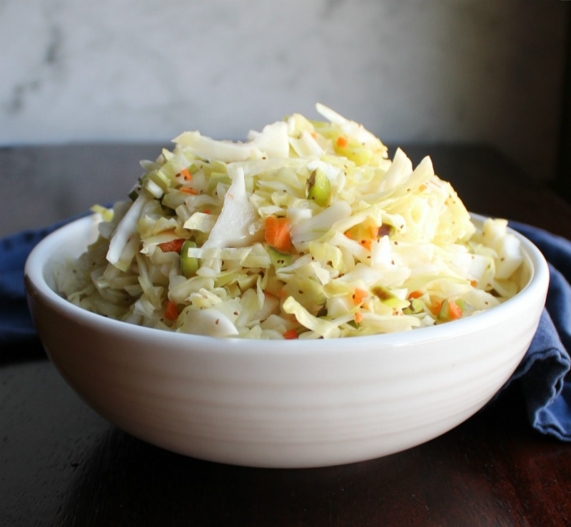 close up of a white serving bowl loaded with tangy vinegar based coleslaw