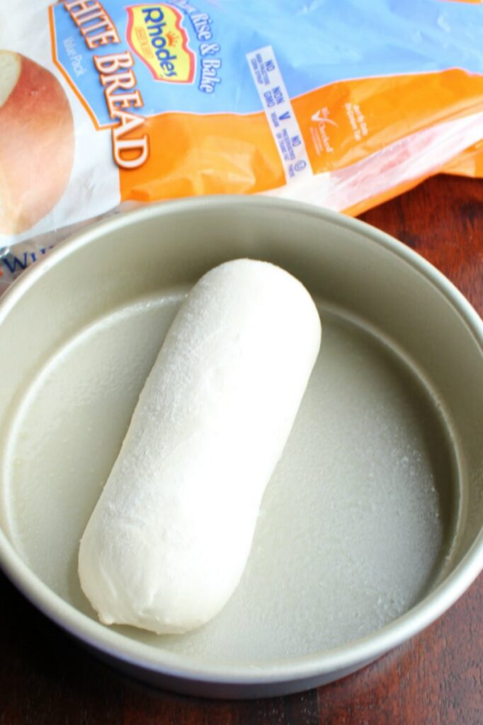 """loaf of frozen bread dough defrosting in 8"""" round cake pan with remaining bag of bread dough in background."""