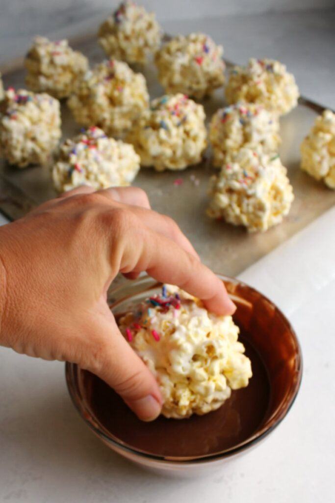 hand dunking marshmallow popcorn ball into bowl of melted milk chocolate.