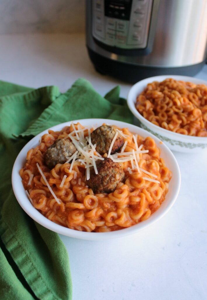 bowl of homemade copycat spaghettios with meatballs and shreds of Parmesan cheese in front of pressure cooker.