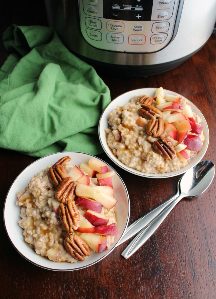 Bowls of maple cinnamon steel cut oatmeal with peaches and pecans in front of pressure cooker.