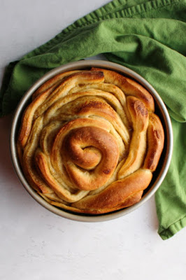 golden brown giant orange cardamom roll fresh from the oven - in cake pan