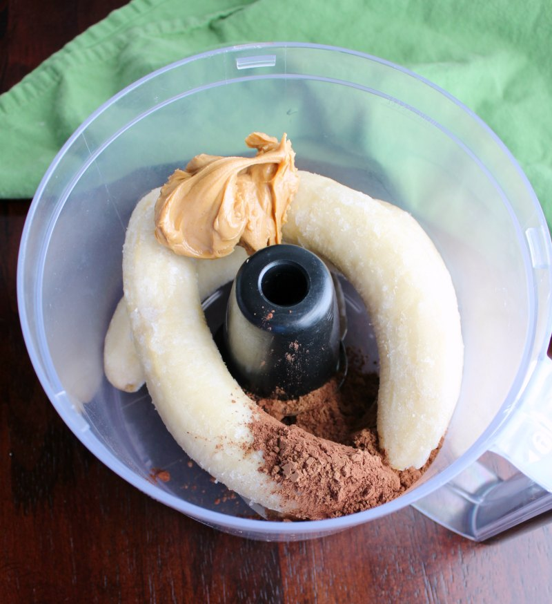 food processor bowl with frozen bananas, peanut butter and cocoa powder for nice cream.