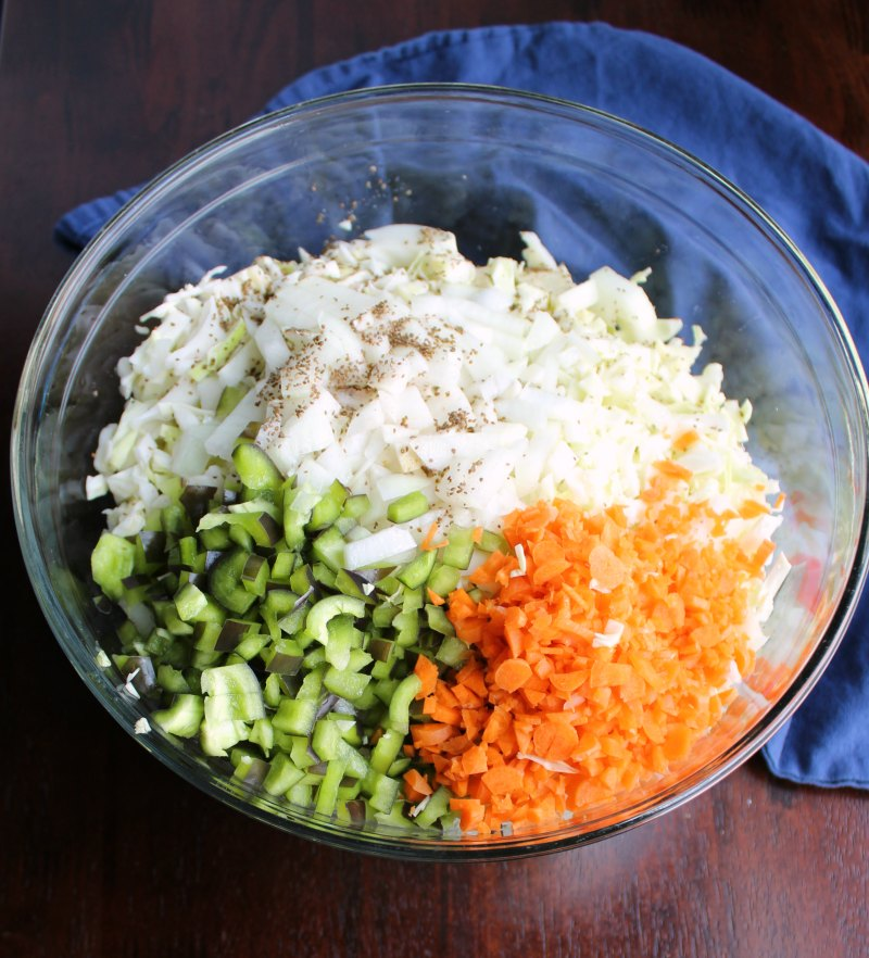 big bowl of shredded cabbage, onions, peppers, carrots and celery seed for coleslaw.