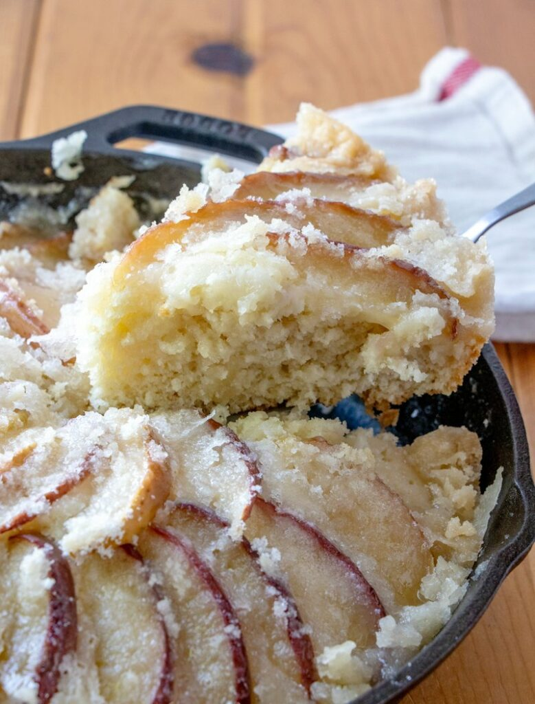 first slice of dutch apple cake being lifted out of cast iron skillet.