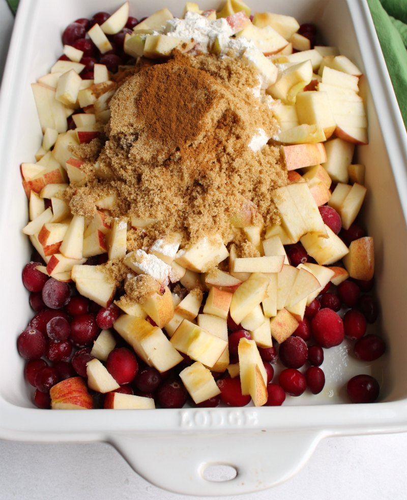 apple and cranberries in baking dish with brown sugar and cinnamon for making crisp.