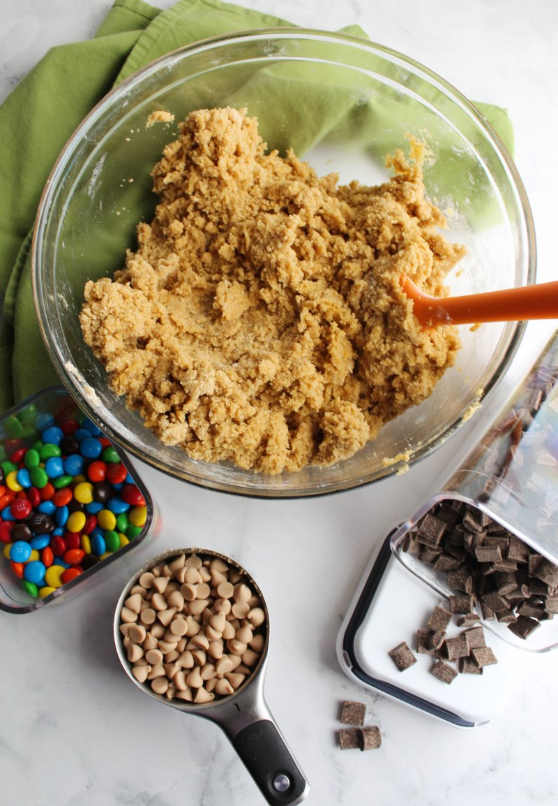 mixing bowl of blondie dough with container of chocolate chunks, m&ms and salted caramel chips in measuring cup