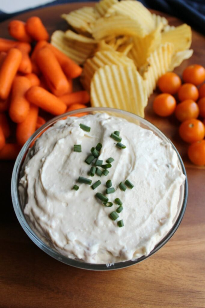 looking down on tray with bowl of creamy clam dip, baby carrots, potato chips and cherry tomatoes